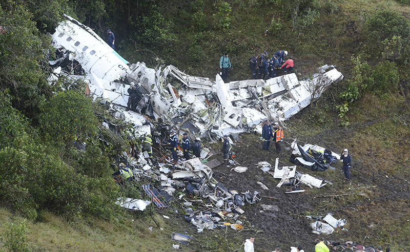 Rescue workers carry a body away from he wreckage of a chartered airplane that crashed in La Union, a mountainous area outside Medellin, Colombia, Tuesday , Nov. 29, 2016. The plane was carrying the Brazilian first division soccer club Chapecoense team that was on it's way for a Copa Sudamericana final match against Colombia's Atletico Nacional. (AP Photo/Luis Benavides)