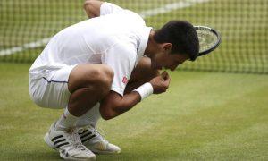 O tenista sérvio Novak Djokovic comemora seu título em Wimbledon em 2015 comendo grama